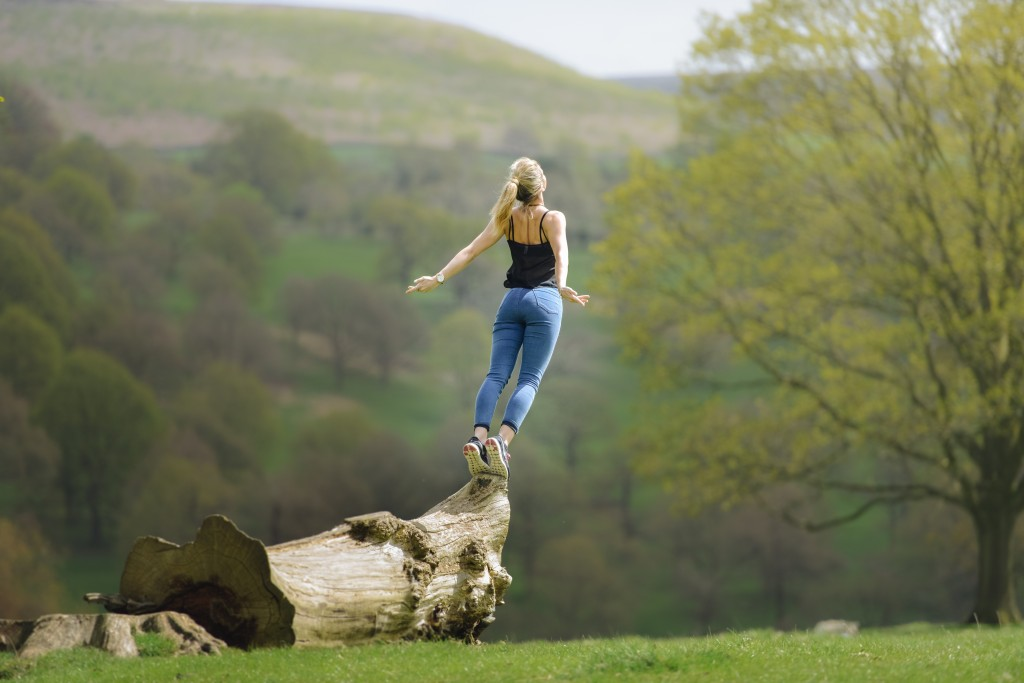 Woman Gracefully Falling & Jumping Of Tree In Field
